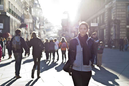 Foto de Urban girl standing out from the crowd at a city street  - Imagen libre de derechos