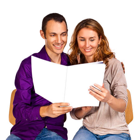 Photo pour Young couple in love reading together a brochure with blank cover pages - image libre de droit