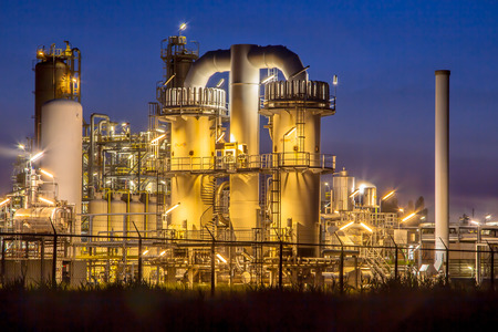 Foto de Detail of a heavy Chemical Industrial plant with mazework of pipes in twilight night scene - Imagen libre de derechos