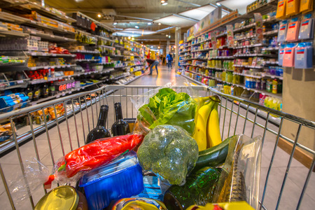 Photo pour Grocery cart at a supermarket aisle filled up with food products seen from the customers point of view - image libre de droit