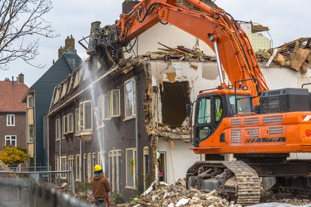 Photo for Orange Demolition crane demolishing old row of houses in the Netherlands - Royalty Free Image