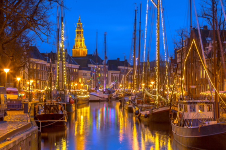 Photo pour Historic sailing ships moored at river quay on the annual Winterwelvaart festival around christmas. Reliving the old times in the historic part of Groningen city. - image libre de droit