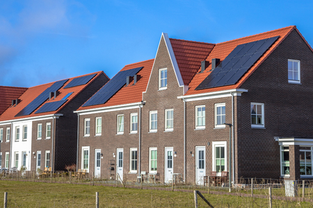 Photo for Modern row houses with solar panels, brown bricks and red roof tiles in neoclassical style in Groningen Netherlands on sunny day - Royalty Free Image