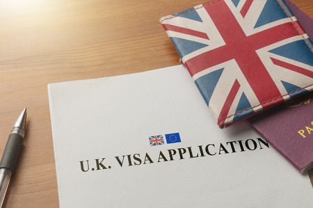 Photo for Visa application on desktop with passport and union jack wallet - Royalty Free Image