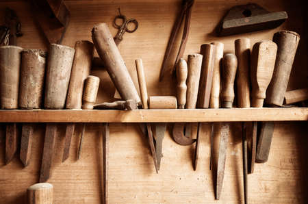 Photo pour Vintage colored image of carpenter tools hanging from the wall of a dusty workshop - image libre de droit