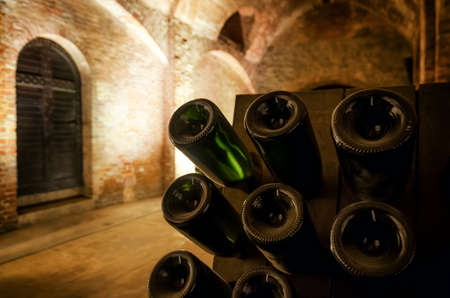 Photo pour Pupitre and bottles inside an underground cellar for the production of traditional method sparkling wines in italy - image libre de droit