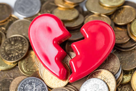 Foto de Broken red Valentines Day heart on a pile of coins. Love and money problems abstract concept. - Imagen libre de derechos