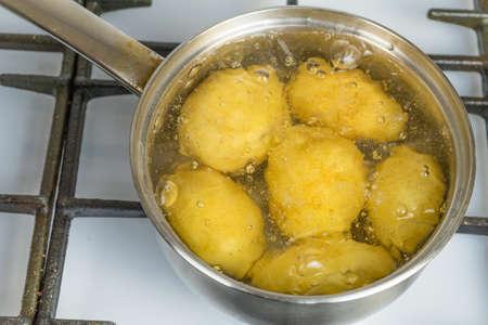 Foto de Untreated potatoes boil in a pot on a gas stove. - Imagen libre de derechos