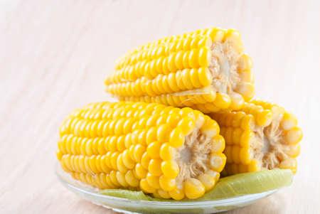 Foto de Three cobs of sweet corn cooked in a dish on a wooden table - Imagen libre de derechos
