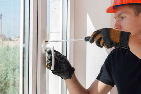 Photo pour master with a screwdriver sets fittings on the window - image libre de droit
