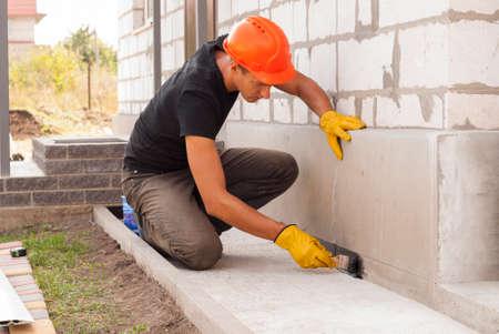 Photo pour worker applies bitumen mastic on the foundation - image libre de droit