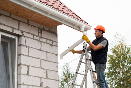 Foto de Worker installs the gutter system on the roof - Imagen libre de derechos