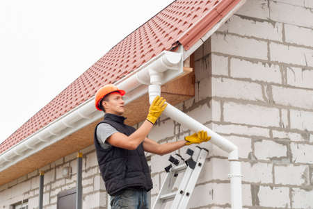 Foto de Construction worker installs the gutter system on the roof - Imagen libre de derechos