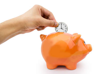 Photo pour hand holding a clock ticking into the piggy bank - image libre de droit