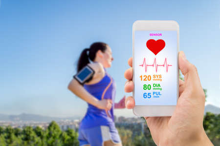 Photo pour male hand holding the smartphone with mobile app health sensor to measure the athlete health. All screen content is designed by my and not copyrighted by others and created with digitizing tablet and image editor.All screen content is designed by us and n - image libre de droit