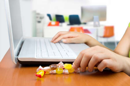 Photo for woman working at the laptop eating a candy sweet - Royalty Free Image