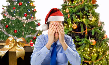 Foto de Stressed man is shopping gifts for christmas with red santa hat angry and distressed - Imagen libre de derechos