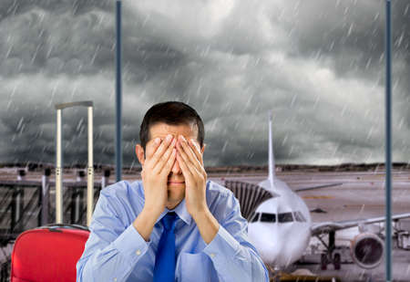 Photo pour businessman crying by delayed flight because the stormy weather at the lobby airport - image libre de droit