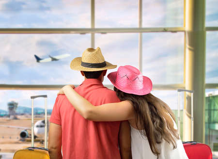 Photo pour affectionate young couple in international airport looking at the airplane - image libre de droit