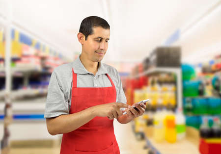 Foto de shopman with pinafore uses a smart phone at the supermarket - Imagen libre de derechos