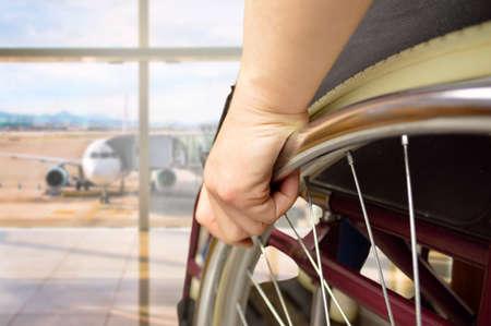 Foto de rear view of a man in wheelchair at the airport with focus on hand - Imagen libre de derechos