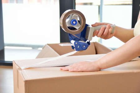 Photo for Shot of an unidentifiable young woman closing a cardboard box with tape at home - Royalty Free Image