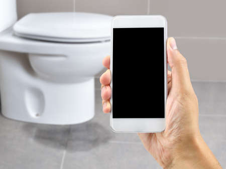 Photo for A hand holding a smartphone to call the professional to repair a water leak in the toilet - Royalty Free Image