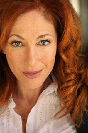 Close-up portrait of an attractive red haired woman with freckles
