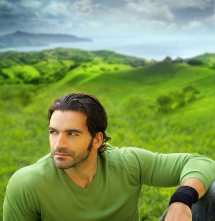 Photo for Portrait of a relaxed good-lookiing young man in beautiful natural setting wearing a green sweater - Royalty Free Image