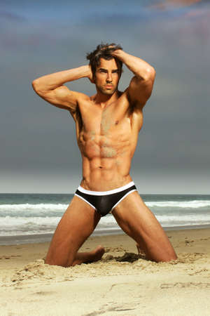 Photo for Sexy male model in fashion swimwear posing on the beach - Royalty Free Image