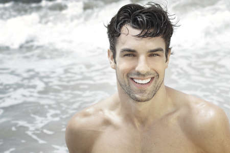 Photo for Handsome happy man smiling with ocean water background - Royalty Free Image