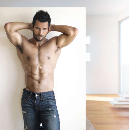 Sexy fashion portrait of a hot male model in stylish jeans with muscular body posing in modern setting