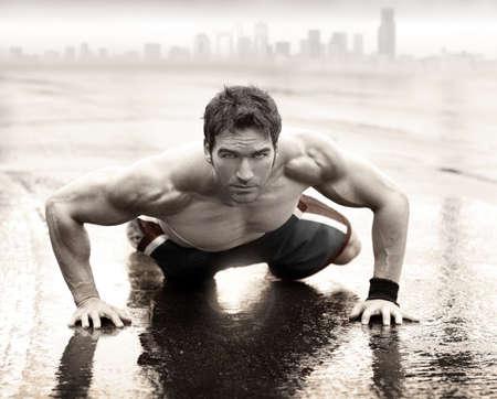 Foto de Sexy fit muscular man doing push-up on wet road with city skyline in the background - Imagen libre de derechos