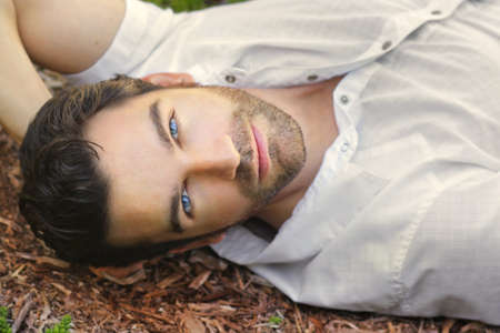 Photo for Portrait of young man outdoors with very handsome face in white casual shirt relaxing outdoors - Royalty Free Image