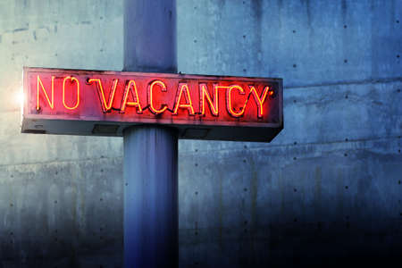 Photo for Glowing retro neon 'no vacancy' sign against cool blue wall background - Royalty Free Image