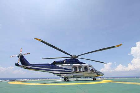 Foto de helicopter parking landing on offshore platform. Helicopter transfer crews or passenger to work in offshore oil and gas industry. - Imagen libre de derechos