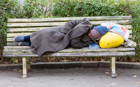 Foto de Sofia, Bulgaria - November 4, 2014: Homeless man is sleeping on a bench in the center of Sofia. Years after joining the EU Bulgaria is still the poorest country in the union. - Imagen libre de derechos