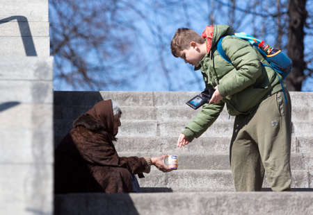 Foto de Sofia, Bulgaria - March 17, 2015: A boy is giving money to a homeless female begger who is begging at the subway underpass stairs in the center of Sofia. - Imagen libre de derechos