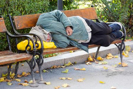 Foto de Homeless person is sleeping on a bench in a cold autumn day in a park in European union's poorest country Bulgaria. - Imagen libre de derechos