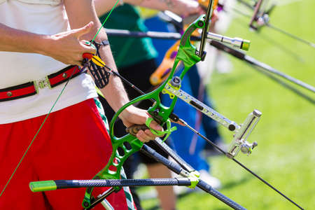 Photo for People are shooting with recurve bows during an archery competition. Hands and bows only. Green bow. - Royalty Free Image
