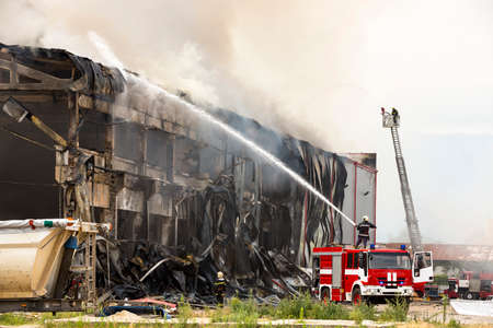 Foto de Fire disaster in a warehouse. Fire fighting in an industrial area. Red fire truck. - Imagen libre de derechos