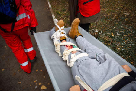 Foto de Paramedics from mountain rescue service provide first aid during a training for saving a person in accident with broken leg. - Imagen libre de derechos