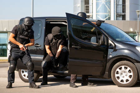 Foto de Customs and border protection officers and Drug enforcement administration special forces participate in a training at the airport for searching and seizing of illegal drugs. Unrecognizable people in black. - Imagen libre de derechos