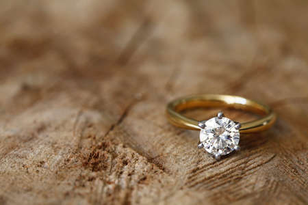 Photo pour Solitaire engagement diamond ring won wooden organic background. - image libre de droit