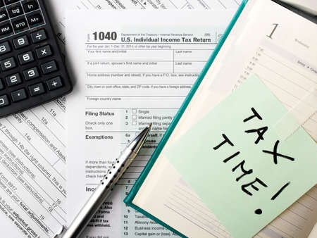 Photo pour Close up U.S. Individual tax form 1040 with calculator and pen. - image libre de droit