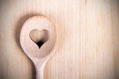 Foto de Heart hole on the wooden spoon pastry board - baking background - Imagen libre de derechos