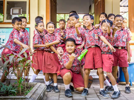 Foto de BALI, INDONESIA - APRIL 25, 2018: Young happy pupils wearing balinese school outfits studying at primary school on Bali island, Indonesia - Imagen libre de derechos