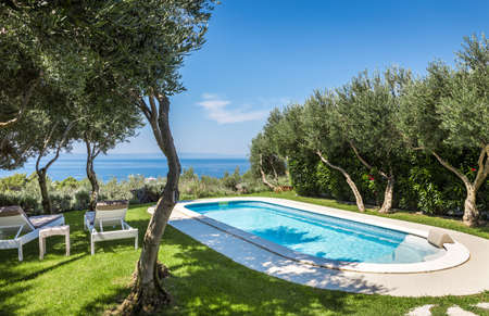 Foto de Private swimming pool with turquoise water and beautiful garden - Imagen libre de derechos