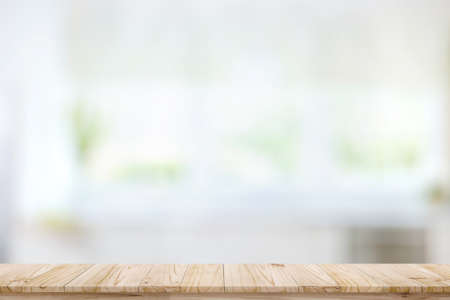 Foto de Empty wood table top on blur kitchen window background. For product or foods montage. - Imagen libre de derechos
