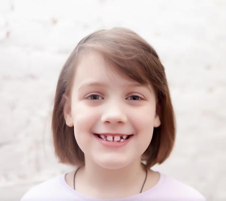 Foto de Portrait of   smiling seven year old girl on   white background. - Imagen libre de derechos